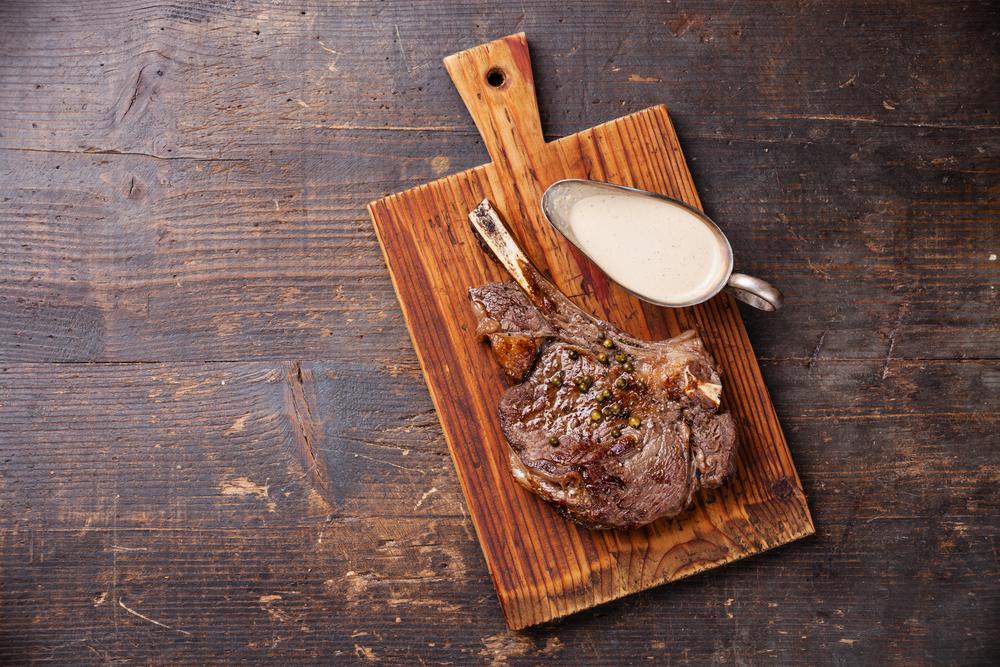Ribeye Steak with pepper sauce on dark wooden background
